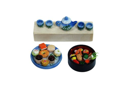 repast: Tea set painted with bamboo shoots, a platter of tea cakes and a bowl of sushi for a relaxing afternoon repast - Path included Stock Photo