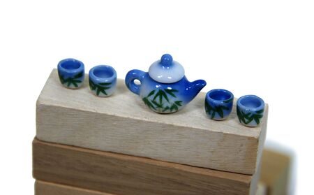 repast: Tea set decorated with bamboo shoots on a wooden plank for a relaxing afternoon repast - Path included