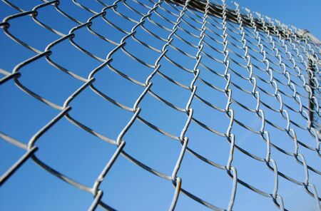 Chain link fence against a deep blue sky serving as a barrier for moving forward