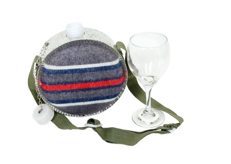 roughing: Camping style canteen with carrying strap to keep hydrated while outdoors and a wine glass  Stock Photo