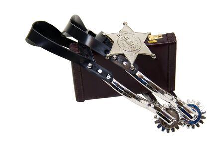 Cowboy spurs and sheriff star in silver and leather on a briefcase to tame a wild business Stock Photo - 4871200