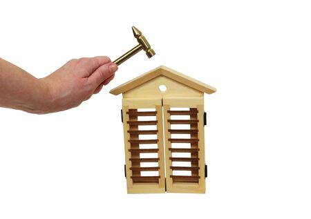 Holding a hammer above a wooden house to represent home repairs - included photo