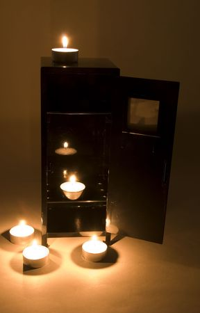 additional: Candle glowing in around a metal locker in the darkness with a dark background