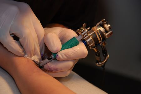 Artist holding a tattoo needle in preparation of drawing ink