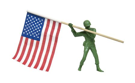 plastic soldier: Soldier as represented by a green plastic model carrying the American Flag - included Stock Photo