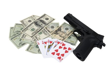 high stakes: High stakes gambling shown by cards, money and a black hand gun