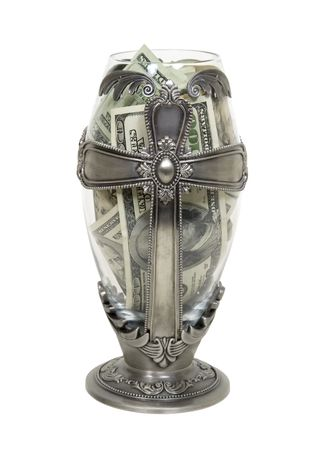 Tall silver cross vessel representing religion filled with large amounts of cash