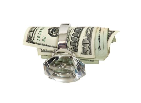 Money and marriage shown by a diamond engagement ring with large bills of money rolled inside