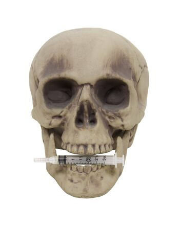 Drug abuse shown by medical syringe used to inject medication in the teeth of a skull - path included