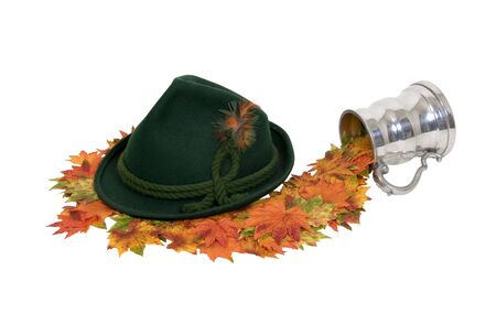 Explore fall traveling shown by stein pouring leaves to a green felt Alpine hat with rope twists and bright feathers