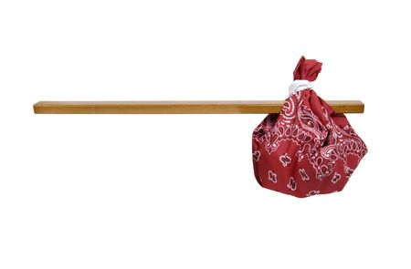 Easy travel kit shown by traditional paisley kerchief bandana tied around a stick of wood Stock Photo - 5589470