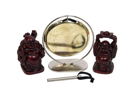 A gong hanging from a frame makes a resonating sound when struck with a beater with two Buddha figurines