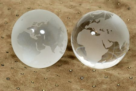 Two different worlds shown by contrasting crystal globes on a leather background
