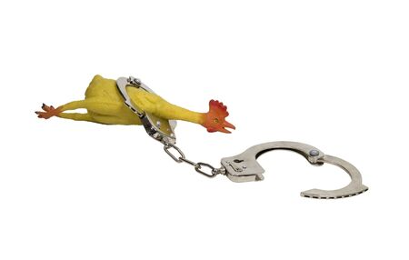 Arresting bad jokes shown by a rubber chicken in a pair of handcuffs - path included Фото со стока