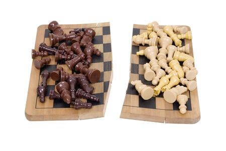 Divided we fall shown by a set of chess pieces divided on a broken wooden chess board - path included Stock Photo