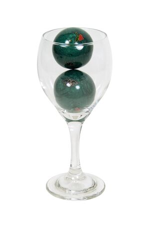 glasswear: Serving of health shown by metal Chinese health balls with simple decorations in a wine glass - path included Stock Photo