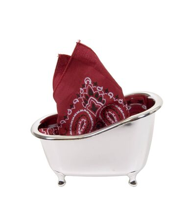 Traditional paisley kerchief bandana used for a variety of purposes in a silver clawfoot bathtub Stock Photo