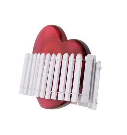 Home is where the heart is shown by a white picket fence around a large red heart photo