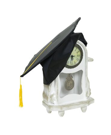 Graduation mortar board with tassel used during ceremonies on a whitewashed mantel clock