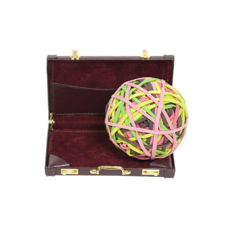 rubberband: Holding business together shown by a rubberband ball in a leather briefcase  Stock Photo