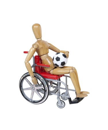 In a wheelchair holding a soccer ball photo