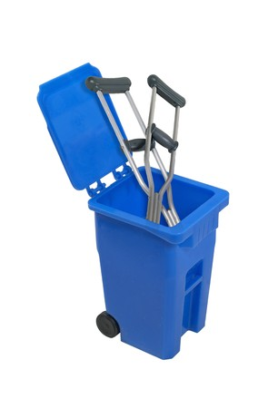 Crutches in a recycle bin used to hold items to be reduced and reused to help the environment - path included