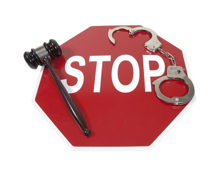 Traffic violations shown by a stop sign with handcuffs and a gavel Stock Photo