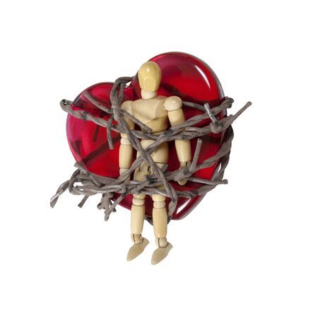 trapped: Trapped by love shown by a model trapped on a red glass heart by barbed wire