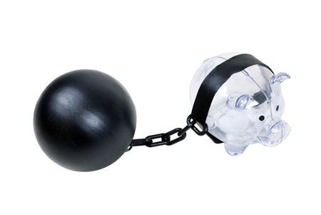 Clear piggy bank used to save change for a future purchase held by a ball and chain - path included photo