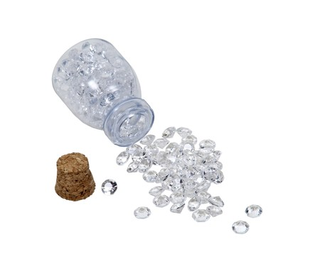 Diamonds with facets that sparkle brightly in the light pouring from a small jar with cork top Stock Photo