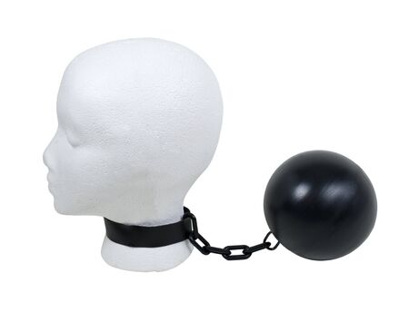 Overcoming struggles shown by a model head with a ball and chain around the neck 版權商用圖片