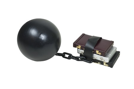 Heavy office security shown by a large metal ball and chain around a stack of briefcases photo