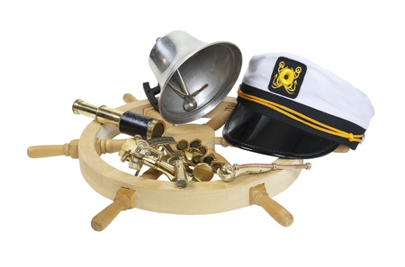 Nautical supplies including ship wheel, captain hat, bell, and an assortment of brass instruments - path included Stock Photo