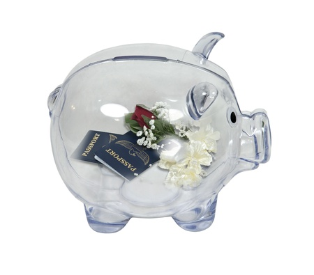 Honeymoon savings shown by a piggy bank in profile with passports with a corsage and boutenniere inside