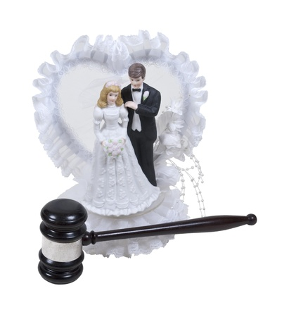 Wedding cake topper with lace and bride and groom with a wooden gavel photo