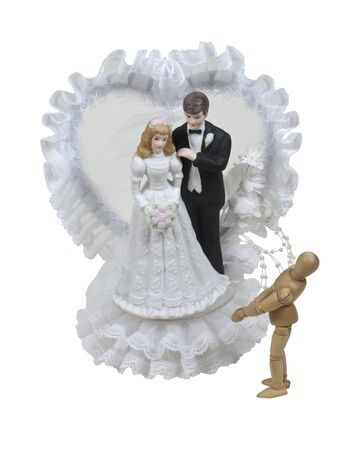 Dreaming of marriage shown by a small model looking up at a bride and groom wedding cake topper - path included