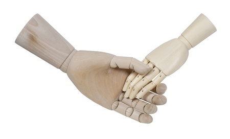 grasping: Wooden model representing a person gently grasping another wooden hand Stock Photo
