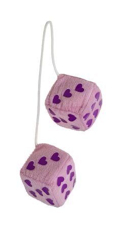 Fuzzy pink heart dice that are usually hung from the rear view mirror of a car