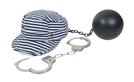 ball and chain: Jailbird striped hat worn in vintage jails as part of the uniform with a pair of handcuffs and ball and chain Stock Photo