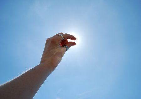 pinch: A pinch of sunshine shown by a hand up in the sky in a pinching motion Stock Photo
