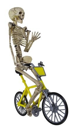 Skeleton riding a yellow bicycle with his hand raised - path included Stock fotó