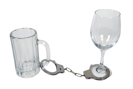 Handcuffs made of metal with mechanical clasp attached to a beer mug and wine glass - path included Stock Photo - 11488186