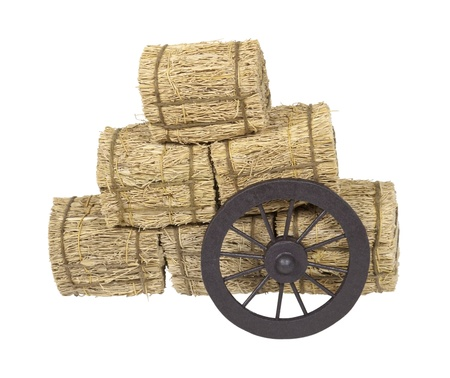 Wooden western stagecoach style wheel leaning on bales of hay - path included