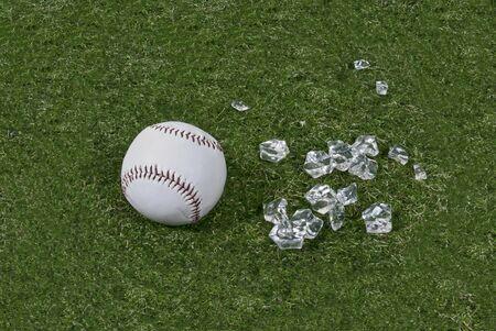 Honkbal en gebroken glas op groen gras