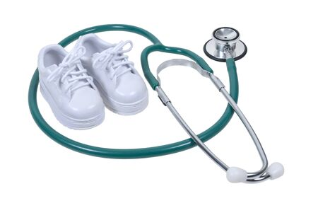 Medical stethoscope and a pair of small white shoes - path included Stock Photo - 14559675