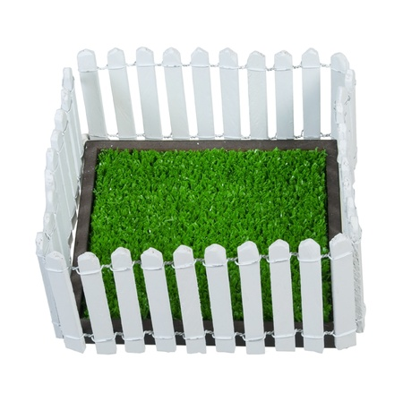 Enclosed green grass yard by a white picket fence photo