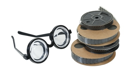 Reels of antique movie film with a set of nerd glasses - path included Stock Photo - 16987498