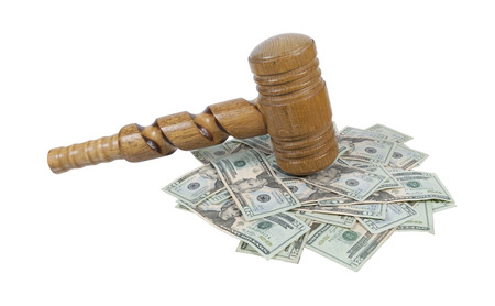 A super sized ceremonial wooden gavel with ornate twists on a pile of money - path included photo