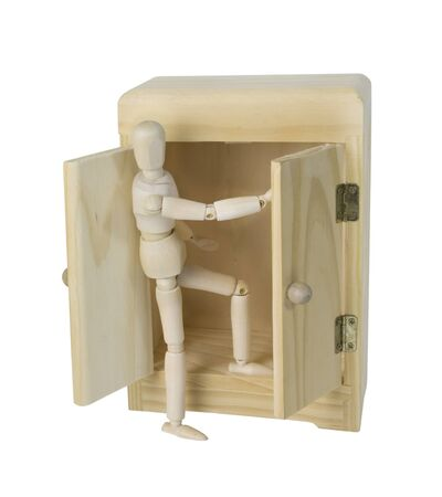 Climbing out of a Wooden wardrobe used to hold clothing in lieu of a closet - path included Stock Photo