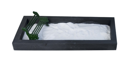 Metal Bench in an enclosed park filled with a white substance, such as snow or sand - path included